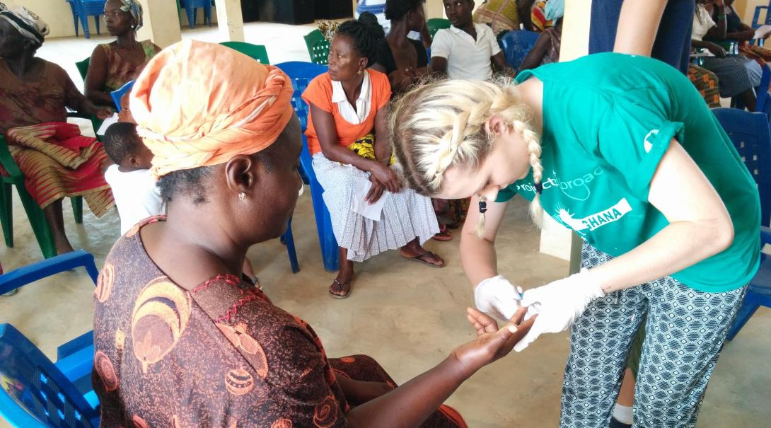 Projects Abroad nursing volunteer is taking a blood sample in Ghana during her internship.